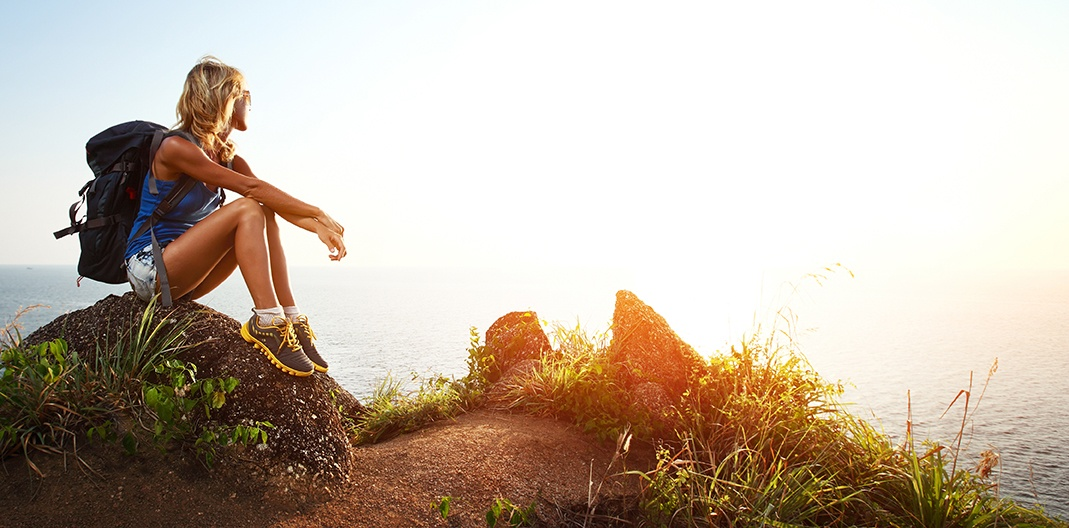 50 year old woman sitting on rock viewing a sunset after hiking